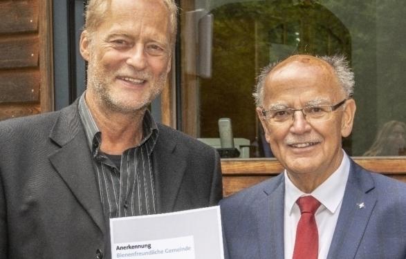 Bienenfreundliche Gemeinde: Gerd Kleiber, Dritter Bürgermeister von Kirchheim, nimmt die Anerkennungsurkunde aus den Händen von Bezirkstagspräsident Josef Mederer (rechts) entgegen. Foto: Wolfgang Englmaier