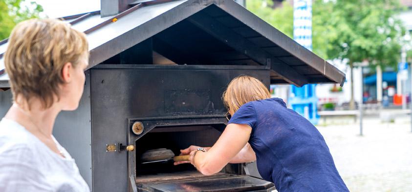 Schieb, schieb in den Ofen rein: Gemeinsames Brotbacken auf dem Pfarrer-Caspar-Mayr-Platz verbindet, schafft ein Gemeinschaftsgefühl und zeugt von einem lebendigen Ortskern. Foto: Claudia Topel