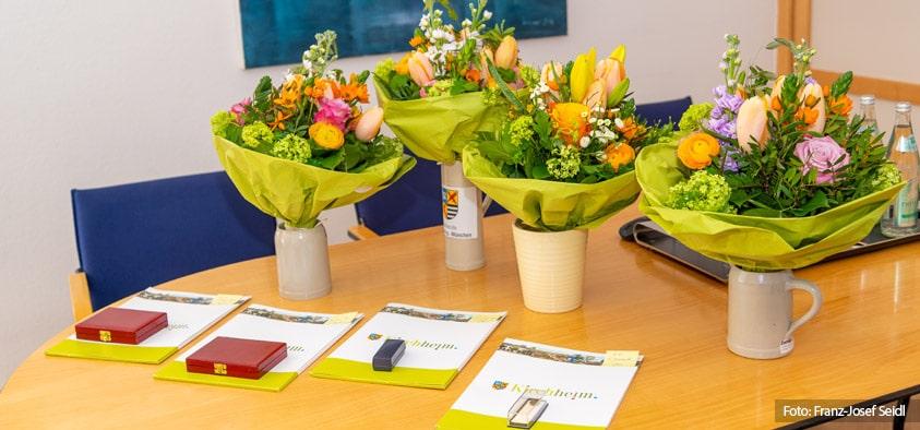 Foto: Blumensträuße, Ehrennadeln- und medaillien für die ehemaligen Gemeinderatsmitglieder.
